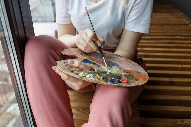 Mani dell'artista con i colori di miscelazione della spazzola sulla fine della tavolozza su Foto Premium