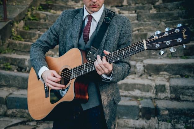 Mani dell'uomo che suonano la chitarra acustica. sfondo autentico. Foto Premium