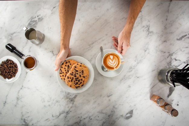 Mani dell'uomo con i biscotti e un cappuccino Foto Gratuite