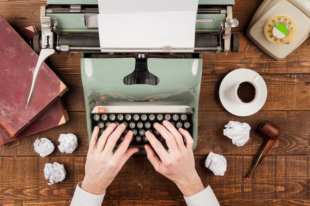 Mani dell'uomo d'affari che scrivono su una vecchia macchina da scrivere Foto Premium