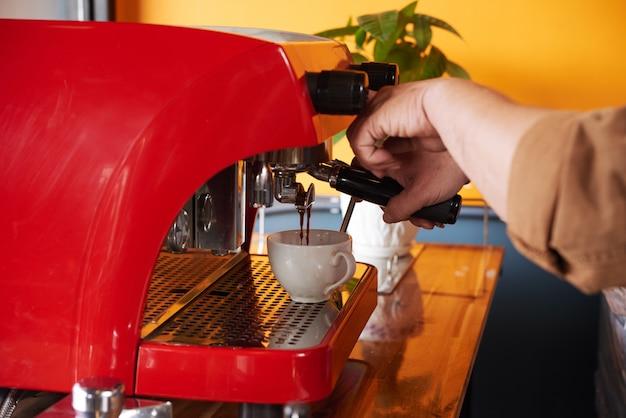 Mani dell'uomo irriconoscibile che fa tazza di caffè sulla macchina del caffè espresso Foto Gratuite