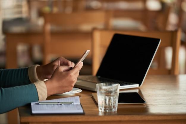 Mani dell'uomo irriconoscibile che utilizza smartphone nel caffè e computer portatile sulla tavola Foto Gratuite