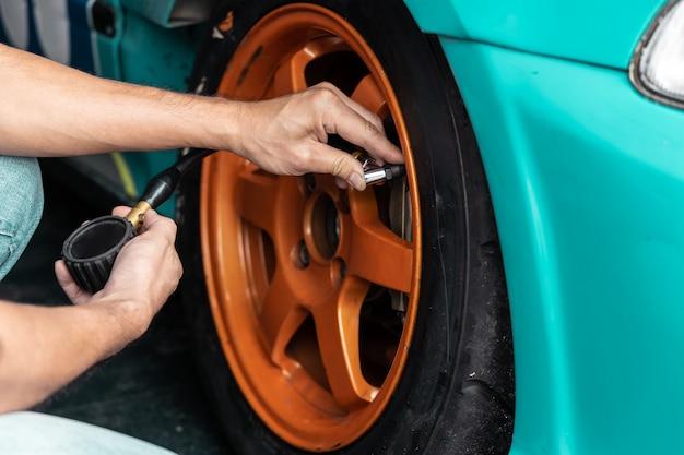 Mani dell'uomo meccanico che controllano la pressione dell'aria della gomma. Foto Premium