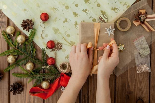 Mani della donna che avvolgono il regalo di natale Foto Premium