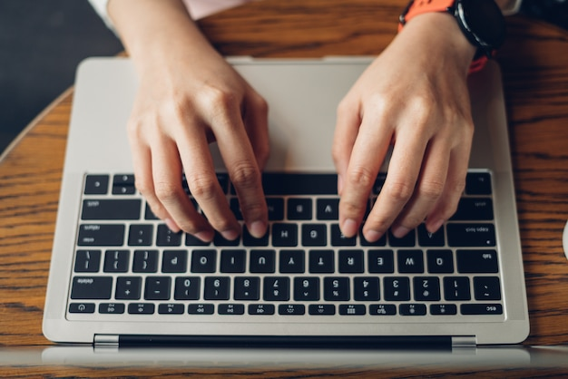 Mani della donna che scrivono sul computer portatile Foto Premium