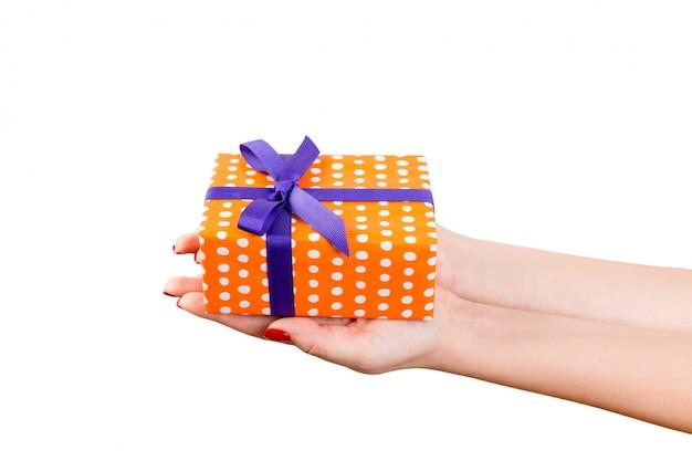 Mani della donna che tengono un contenitore di regalo avvolto Foto Premium