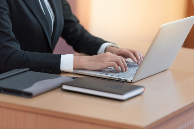 Mani della donna di affari che digitano sulla tastiera del computer portatile allo scrittorio. Foto Premium