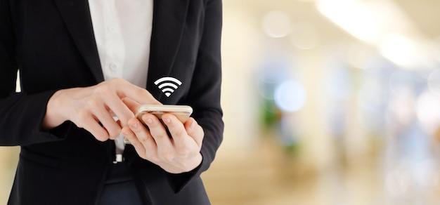 Mani della donna di affari facendo uso dello smart phone con l'icona di wifi sopra l'ufficio della sfuocatura con la luce del bokeh Foto Premium