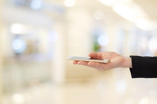 Mani della donna di affari facendo uso dello smart phone sopra l'ufficio della sfuocatura con il fondo della luce del bokeh, insegna, affare sul telefono Foto Premium