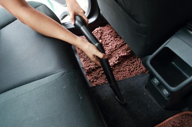 Mani della donna facendo uso dell'automobile interna dell'aspirapolvere Foto Premium