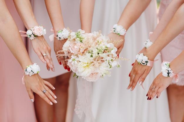 Mani della sposa e damigelle con fiori in ombra rosa Foto Premium