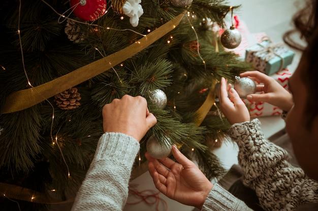 Mani delle coppie che mettono i giocattoli sull'albero di natale Foto Gratuite