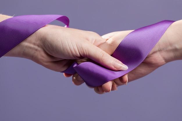 Mani delle donne che tengono il nastro di raso viola Foto Gratuite