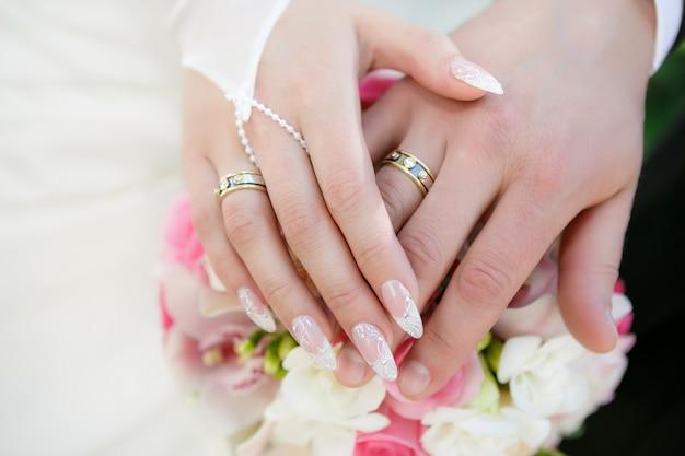 Mani dello sposo e la sposa con fedi nuziali e un bouquet da sposa di rose Foto Premium