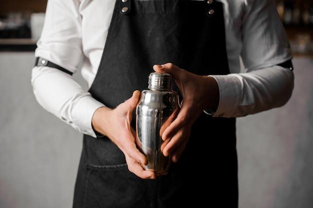 Mani di baristi in possesso di un agitatore contro il bancone del bar Foto Premium