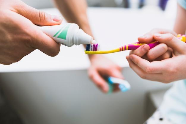 Mani di close-up mettendo dentifricio sulla spazzola Foto Gratuite