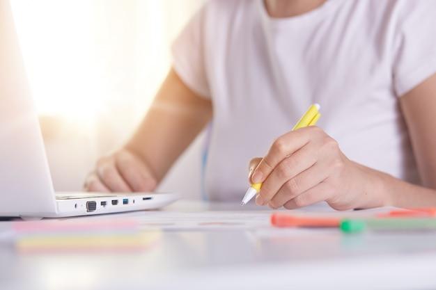 Mani di donna con penna gialla scrivendo qualcosa su peper, lavorando online, femmina lavorando sul computer portatile Foto Gratuite