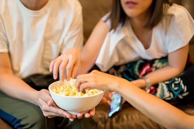Mani di donna prendendo popcorn da una ciotola guardando film con un amico. Foto Premium