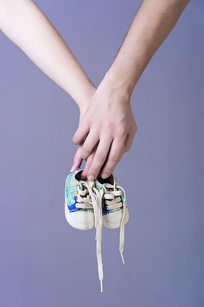 Mani di genitori in attesa che tengono un paio di scarpe da ginnastica per neonati Foto Premium