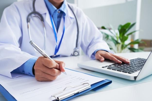 Mani di medico femminile irriconoscibile scrivendo sulla forma e digitando sulla tastiera del computer portatile Foto Gratuite