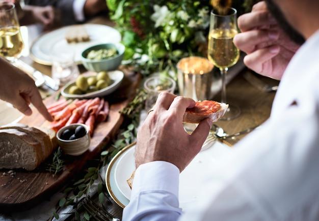 Mani di persone mangiare cibo con banchetti di amici Foto Premium