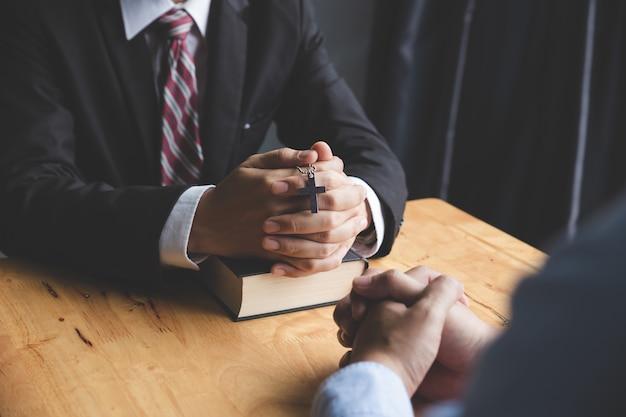 Mani di pregare giovane e bibbia su uno scrittorio di legno Foto Premium