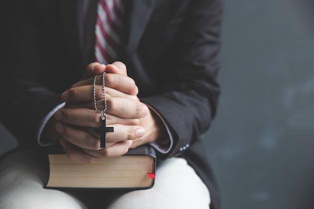 Mani di pregare giovane e scrittorio della bibbia Foto Premium