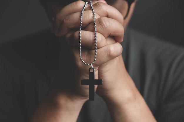 Mani di pregare giovane sulla scrivania Foto Premium