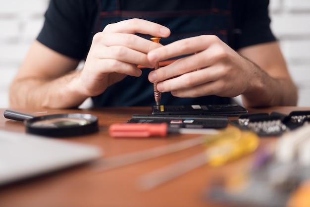 Mani di riparazione smartphone con cacciavite per computer. Foto Premium