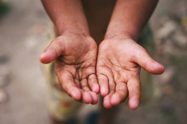 Mani di un bambino senzatetto, implorando palme, accattonaggio mano, uomo affamato. Foto Premium