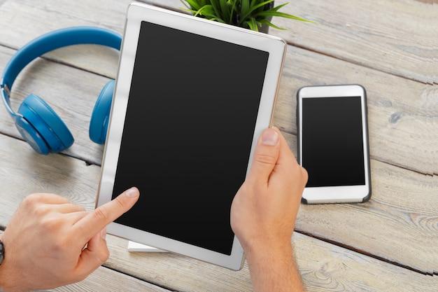 Mani di un dispositivo della compressa della tenuta dell'uomo sopra una tavola di legno dell'area di lavoro Foto Premium