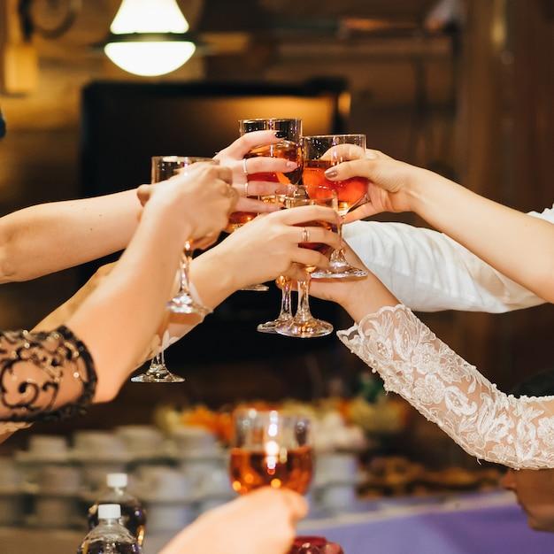 Mani di un gruppo di persone che tintinnano e tostano bicchieri di vino rosso a una festa in un ristorante Foto Premium