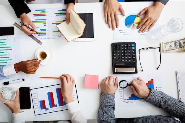 Mani di uomini d'affari sul tavolo bianco con documenti e bozze Foto Gratuite