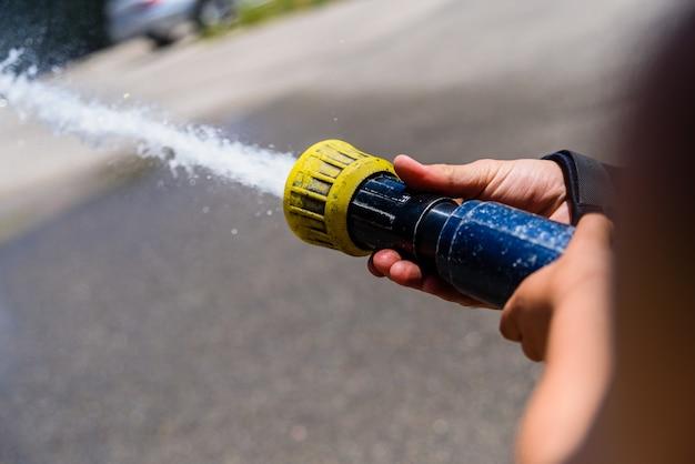 Mani di vigile del fuoco, senza volto, con in mano un tubo facendo gettare acqua ad alta pressione. Foto Premium