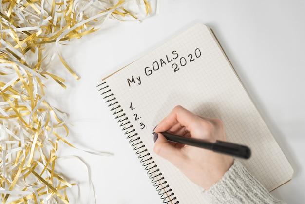 Mani femminili che scrivono my goals 2020 in un taccuino, tinsel, concetto di capodanno Foto Premium