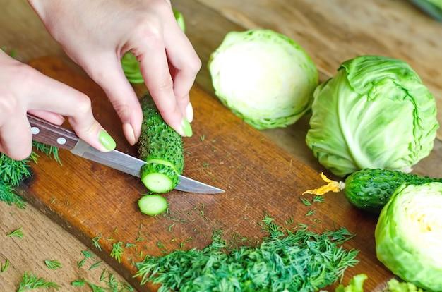 Mani femminili che tagliano i cetrioli verdi freschi su un tagliere di legno Foto Premium