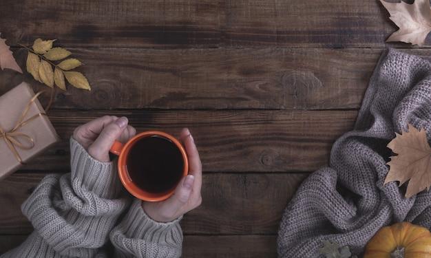 Mani femminili che tengono caffè caldo su fondo di legno Foto Premium