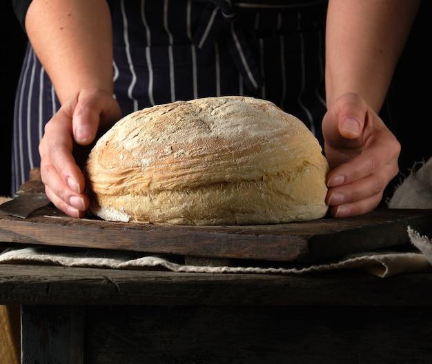 Mani femminili che tengono intorno al pane cotto al forno della farina di frumento sopra la tavola di legno Foto Premium