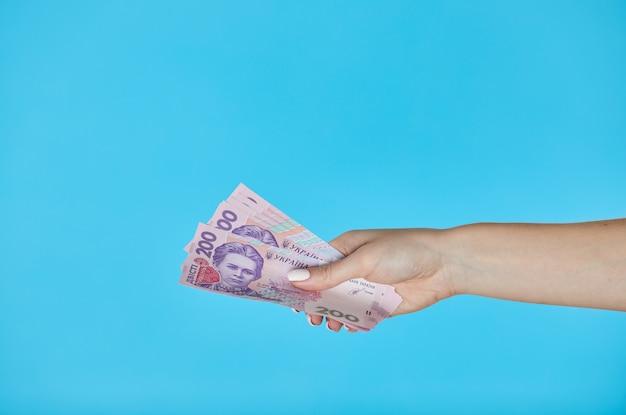 Mani femminili che tengono le banconote ucraine sul blu Foto Premium