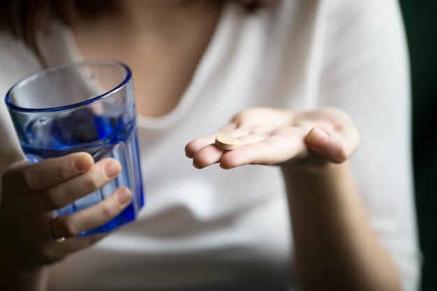 Mani femminili che tengono pillola e bicchiere d'acqua, vista del primo piano Foto Gratuite