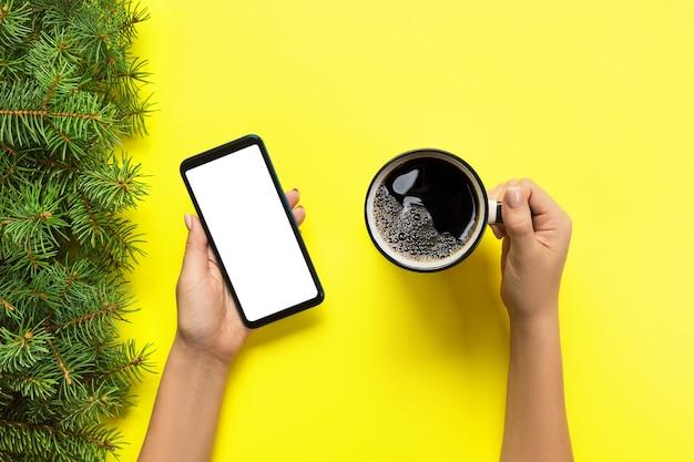 Mani femminili che tengono telefono cellulare nero con lo schermo e la tazza di caffè bianchi in bianco. immagine del modello con copyspace. vista dall'alto su sfondo giallo, piatto disteso Foto Premium