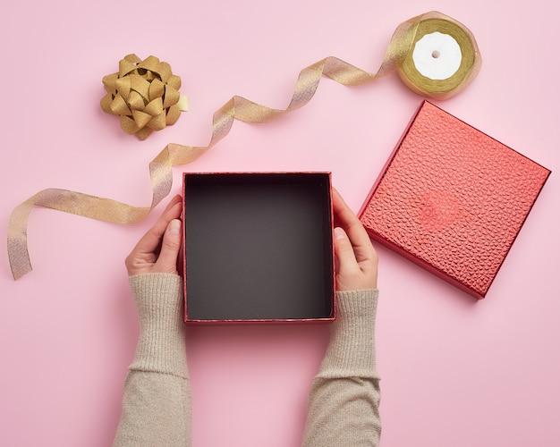 Mani femminili che tengono un contenitore di regalo vuoto quadrato Foto Premium