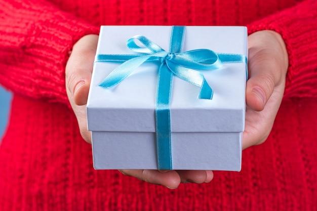 Mani femminili che tengono un piccolo contenitore di regalo bianco avvolto con il nastro blu. per dare e ricevere regali Foto Premium