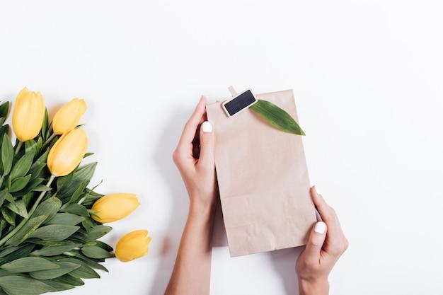 Mani femminili che tengono un sacco di carta con un regalo vicino al mazzo dei tulipani gialli su un fondo bianco Foto Premium