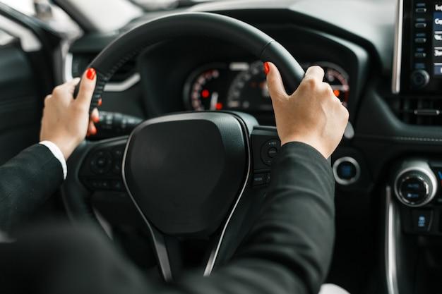 Mani femminili che tengono un volante nel salone dell'automobile. Foto Premium