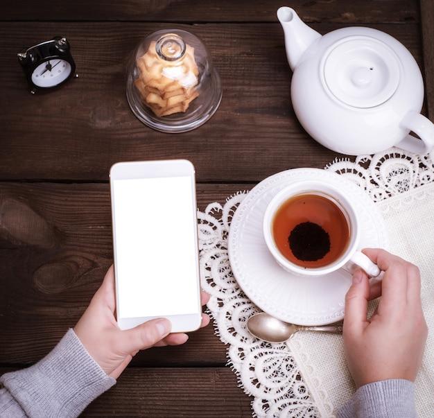 Mani femminili che tengono uno smartphone bianco Foto Premium