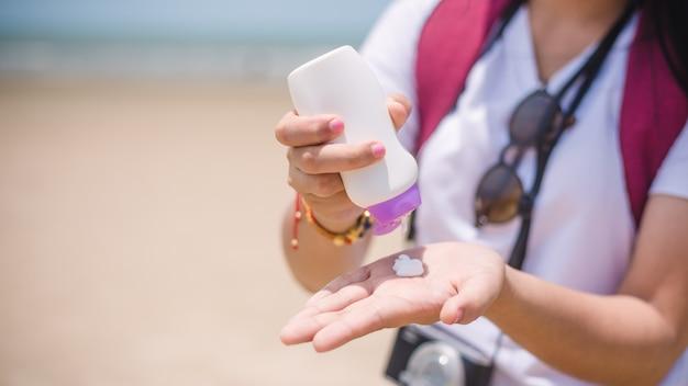 Mani femminili con crema protezione solare in spiaggia concep di cura della pelle Foto Premium