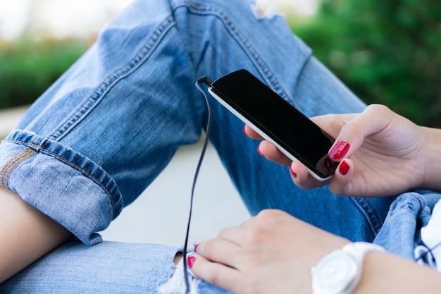 Mani femminili con il manicure rosso che tiene un telefono cellulare con le cuffie collegate Foto Premium
