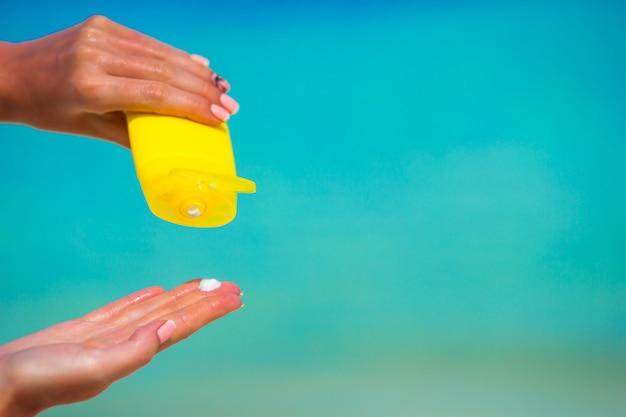Mani femminili con il mare del blu del fondo della bottiglia della crema solare Foto Premium