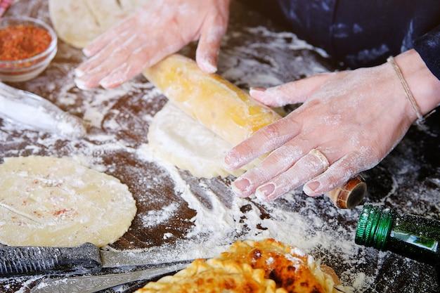 Mani femminili cuocere stendere la pasta con un mattarello sul tavolo, cosparsi di farina. Foto Premium